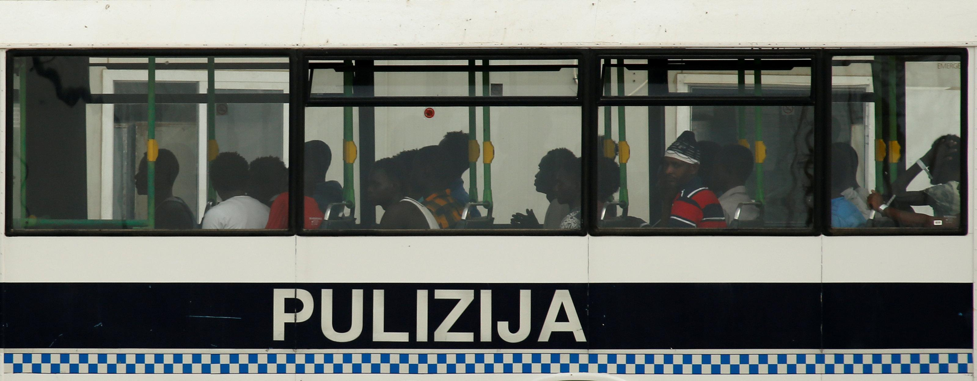 Migrants who were rescued by the Armed Forces of Malta (AFM) some 53 nautical miles south of Malta sit in a police bus as it leaves the AFM maritime squadron base in Valletta