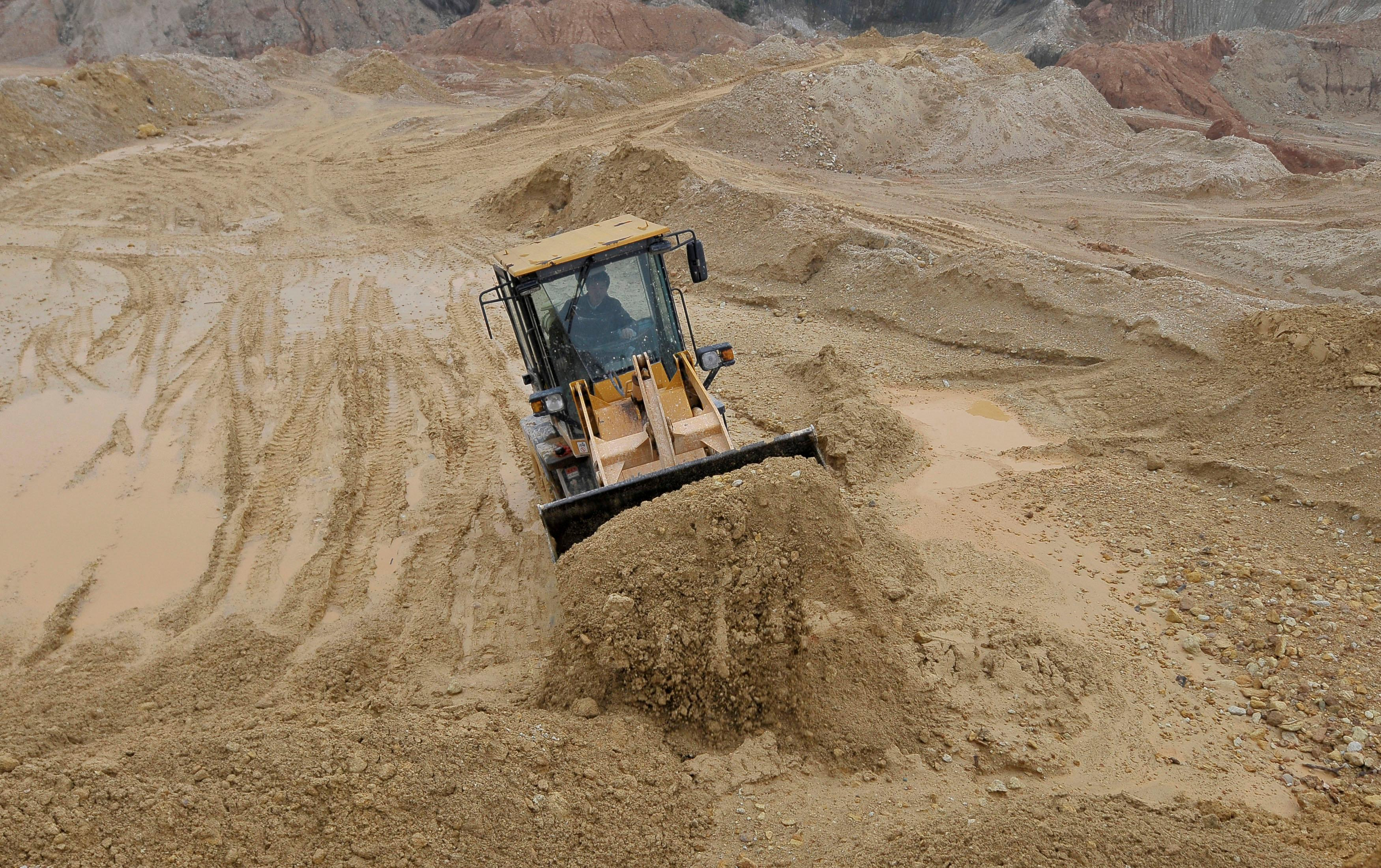 A labourer operates a bulldozer at a site of a rare earth metals mine at Nancheng county, Jiangxi province,China March 14, 2012. Stringer