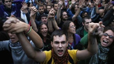 """Demonstrators chant """"These are our weapons"""" as they hold up their hands after riot police charged them outside the Spanish parliament in Madrid, September 25, 2012. REUTERS/Susana Vera"""