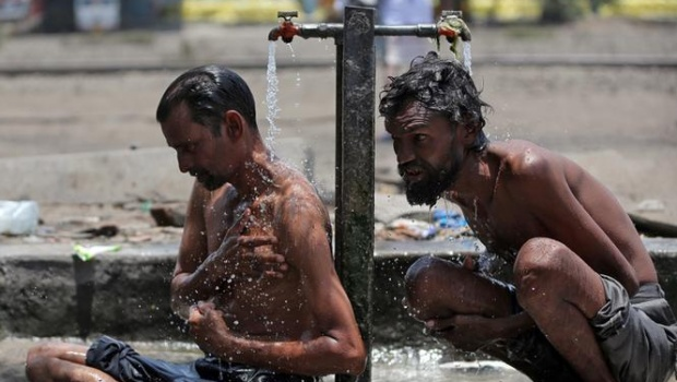 Men bathe at municipal taps along railway tracks, at a yard, on a hot day in Ahmedabad, May 27, 2018. REUTERS/Amit Dave