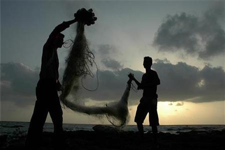 Fishermen fold their fishing nets in Mumbai May 9, 2007. A group of 125 international marine scientists urged the head of the World Trade Organisation (WTO) on Thursday to push for a global accord to slash subsidies paid by many countries to their fishing industries. REUTERS/Sima Dubey