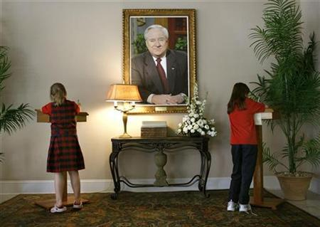 Two girls sign the book of condolence at the Thomas Road Baptist Church after its founder Reverend Jerry Falwell, whose portrait is seen here, died in Lynchburg, Virginia, May 17, 2007. REUTERS/Joshua Roberts