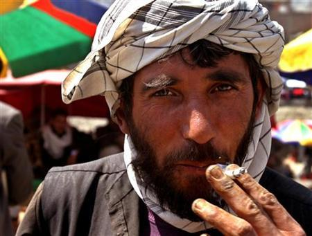 An Afghan man smokes a cigarette in Kabul in this April 17, 2005 file photo. Afghanistan may be the world's largest producer of heroin, but the government has taken the first step towards to a ban on smoking in public places. REUTERS/Ahmad Masood