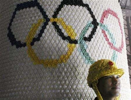 A worker stands in front of a decorative poster of the Olympic rings made with condoms for the upcoming 4th China Reproductive Health New Technologies and Products Expo, in Beijing, July 10, 2007. REUTERS/Ge Gong