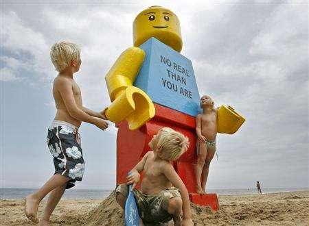Children play near a giant smiling Lego man that was fished out of the sea in the Dutch resort of Zandvoort August 7, 2007. REUTERS/Marco de Swart