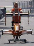 <p>Mecânico da Spyker transporta pedaços de um carro da equipe em Xangai, dia 4 de outubro. A montadora holandesa de carros esportivos Spyker Cars NV chegou a um acordo final para vender sua equipe de Fórmula 1 a um consórcio, por 88 milhões de euros. Photo by Claro Cortes Iv</p>