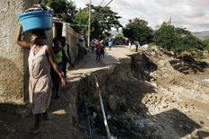 <p>Haitianos andam junto a estrada destruída pela chuva em Cabaret, Haiti, 12 de outubro. O Conselho de Segurança da ONU renovou na segunda-feira por mais um ano o mandato da sua força de paz no Haiti, mas a reconfigurou para melhorar a segurança nas fronteiras do país. Photo by Reuters</p>