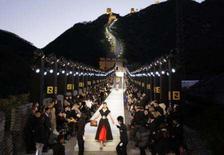<p>Modelo usando um vestida da grife Fendi deixa a passarela montada na Muralha da China durante o pôr do sol, perto de Pequim. Erguida séculos atrás para manter as hordas bárbaras fora do país, a Grande Muralha da China ficou iluminada na sexta-feira com o primeiro grande desfile de moda de sua história. Photo by David Gray</p>