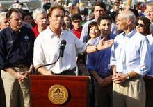 <p>O governador da Califórnia, Arnold Schwarzenegger (centro), agradece ajuda do secretário norte-americano de Segurança Nacional, Michael Chertoff (direita), em San Diego. Há poucos anos, Arnold Schwarzenegger teria colocado um capacete de bombeiro, empunhado uma mangueira e posado para fotos em visita à área atingida pelos incêndios descontrolados da Califórnia. Photo by Mike Blake</p>