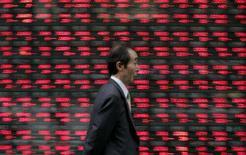 <p>Pedestre passa em frente a painel com cotação de ações, em Tóquio. A bolsa de Tóquio atingiu nesta quarta-feira o ponto mais baixo em sete semanas, encerrando em queda pela terceiro dia consecutivo depois que os ganhos foram pressionados pela valorização do iene. Photo by Michael Caronna</p>