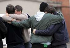 <p>Parentes não identificados do torcedor da Lazio assassinado Gabriele Sandri se abraçam diante do carro em que ele foi assassinado, no domingo. Photo by Stringer</p>