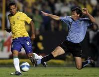 <p>Brasileiro Luis Fabiano recebe a marcação do uruguaio Diego Godin durante partida no Morumbi, em São Paulo, na quarta-feira. O Brasil venceu o jogo pot 2 x 1. Photo by Paulo Whitaker</p>