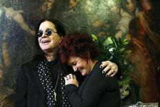 <p>Ozzy and Sharon Osbourne smile as they pose in front of some of their belongings to be auctioned in Beverly Hills, California, November 26, 2007. The Osbournes raised more than $800,000 for charity after heavy metal enthusiasts turned out en masse for their Beverly Hills-style garage sale, auction manager Darren Julien said on Saturday. REUTERS/Mario Anzuoni</p>
