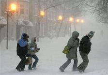 <p>People walk in the street during a snow storm of Quebec City December 16, 2007. REUTERS/Mathieu Belanger</p>
