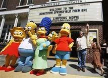 """<p>Creator of the show """"The Simpsons"""" Matt Groening (R) waves alongside characters (L-R) Lisa, Homer, Marge, Maggie, and Bart Simpson as he arrives for the premiere of the film """"The Simpsons Movie"""" in Springfield, Vermont July 21, 2007. In one of the biggest DVD promotions this year, 20th Century Fox is kicking off Tuesday's DVD release of """"The Simpsons Movie"""" with events in cities around the country. REUTERS/Lucas Jackson</p>"""