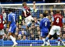 <p>O jogador do Aston Villa Martin Laursen (centro) marca gol contra o Chelsea, em Londres. O Aston Villa arrancou um empate por 4 x 4 com o Chelsea, nesta quarta-feira, numa partida eletrizante que marcou o início da rodada de feriado do Campeonato Inglês. Photo by Dylan Martinez</p>