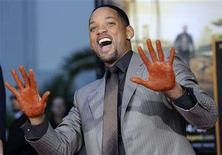 """<p>Actor Will Smith shows off his hands after putting them in cement during a ceremony at Grauman's Chinese Theatre in Los Angeles in this December 10, 2007 file photo. A handful of holiday season hits, led by Smith's sci-fi thriller """"I Am Legend,"""" propelled the movie business out of its fall slump and set the stage for 2007's theatrical film revenues to surpass the 2004 benchmark of $9.45 billion. REUTERS/Chris Pizzello/Files</p>"""