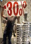<p>Immagine d'archivio di un negoziante che prepara la vetrina per i saldi. REUTERS/Jean-Paul Pelissier (FRANCE)</p>