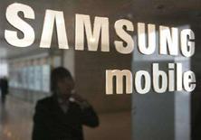 <p>Una donna al telefono riflessa su un vetro col logo Samsung. REUTERS/You Sung-Ho (SOUTH KOREA)</p>