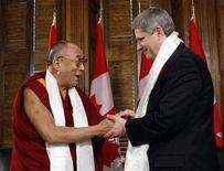 <p>Canada's Prime Minister Stephen Harper (R) shakes hands with Tibet's exiled spiritual leader the Dalai Lama after receiving a scarf at the start of their meeting in Harper's office on Parliament Hill in Ottawa October 29, 2007. Canada has emerged largely unscathed from its brush with Beijing after Harper met the Dalai Lama in October, Canadian International Trade Minister David Emerson said on Monday. REUTERS/Chris Wattie</p>