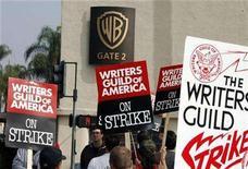 <p>Members of the Writers Guild of America carry picket signs as they cross an intersection at Warner Bros. Studios in Burbank, California November 5, 2007. Up to 1,000 employees on the Warner Bros. lot in Burbank could be laid off anytime after Friday as a result of the Hollywood writers strike. REUTERS/Fred Prouser</p>