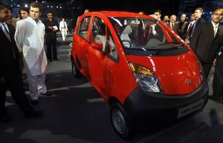 Rahul Gandhi (L in white) of the Congress party stands next to Tata Group's new ''Nano'' car after its launch at the 9th Auto Expo in New Delhi January 10, 2008. REUTERS/Adnan Abidi