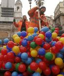 <p>Operatori del Comune di Roma tolgono le palline colorate dalla scalinata di Piazza di Spagna. REUTERS/Remo Casilli (ITALY)</p>