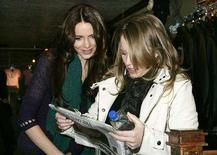 """<p>Amy Redford (R) director of the film """"The Guitar"""" which is in competition at the 2008 Sundance Film Festival, and her film's star, actress Saffron Burrows look at a newspaper article mentioning their film in Park City, Utah, January 18, 2008. Redford is the daughter of the festival's founder, actor and director Robert Redford. The festival will run for 10 days with 121 feature-length films selected for competition. REUTERS/Fred Prouser</p>"""