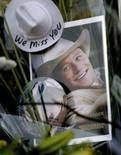 <p>Uma foto do ator australiano Heath Ledger entre as flores deixada em sua homenagem pelos fãs em frente ao edifício onde Ledger foi encontrado morto na terça-feira. Ledger estava irritado e agitado durante as festas de fim de ano porque não podia estar com sua filha, Matilda, segundo a modelo Sophie Ward, amiga dele. Photo by Nicholas Roberts</p>