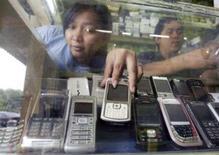<p>Selon le cabinet spécialisé IDC, la croissance des ventes mondiales de téléphones portables devrait ralentir pour tomber sous le seuil de 10% en 2008, après une hausse de 11,6% au quatrième trimestre 2007, au cours duquel plus de 300 millions de combinés ont été écoulés. /Photo d'archives/REUTERS/Crack Palinggi</p>