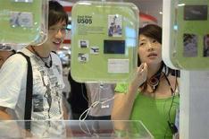<p>Visitatori di uno stand di lettori Mp3 JoyTone U820 presso Power Quotient International a Taipei. REUTERS/ Pichi Chuang</p>