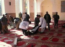 <p>Afghans carry bodies from inside a mosque after a suicide blast in Lashkar Gah city in the southern Helmand province, January 31, 2008. REUTERS/Abdul Qodus</p>
