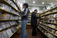 <p>Customers look at pirated DVDs and music CDs at a shop in Beijing October 18, 2007. Canada has joined China and Russia on the U.S. software, music and movie industries' annual list of countries with the worst record of fighting piracy of copyright goods, an industry coalition said on Monday. REUTERS/Claro Cortes IV</p>
