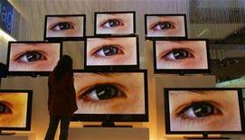 <p>A woman stands in front of flat screens at an exhibition stand of the IFA 2007 consumer electronics fair in Berlin August 30, 2007. An estimated 21 million households have TV sets that receive only over-the-air signals, and about 14 million of those homes rely solely on analog TVs, according to Nielsen Media Research. For viewers who don't upgrade to digital-ready TVs or set-top converters, February 18, 2009, will begin with a blank screen. REUTERS/Hannibal Hanschke</p>