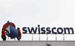 <p>Lavoratori montano il nuovo logo di Swisscom sopra la sede di Worblaufen, vicino Berna. REUTERS/Pascal Lauener (SWITZERLAND)</p>