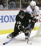 <p>Anaheim Ducks' Corey Perry (L) controls the puck as Edmonton Oilers' Tom Gilbert defends during their NHL game in Anaheim, California December 2, 2007. REUTERS/Danny Moloshok</p>