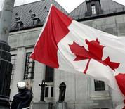 <p>In an undated photo a worker lowers a Canadian flag in front of the Supreme Court of Canada, which contains the two court rooms used by the Federal Court. REUTERS/Jim Young</p>
