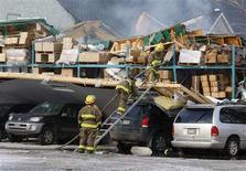 <p>Firefighters work at the scene, where the roof of a bakery warehouse collapsed, in Morin Heights, Quebec March 12, 2008. Emergency workers are trying to rescue three people trapped inside the warehouse after heavy snow caused its roof to collapse, sparking a fire in a Quebec town north of Montreal, provincial police said on Wednesday. REUTERS/Shaun Best</p>