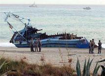 <p>Agenti della Guardia di Finanza ispezionano una barca utilizzata da immigrati clandestini per sbarcare in Italia. REUTERS/Stringer (ITALY)</p>
