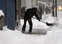 <p>A worker clears snow from in front of a building in downtown Montreal, December 3, 2007. REUTERS/Shaun Best</p>