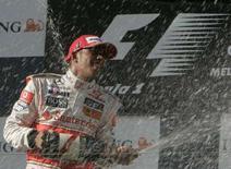 """<p>Льюис Хэмилтон открывает шампанское после победы на первом этапе чемпионата мира по автогонкам в классе """"Формула 1"""", 16 марта 2008 года. Британский пилот Люис Хэмилтон из команды """"Макларен"""" стал победителем первого этапа чемпионата мира по автогонкам в классе """"Формула 1"""" 2008 года, выиграв в воскресенье """"Гран-при Австралии"""". REUTERS/Steve Holland</p>"""