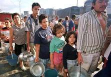 <p>Abitanti di un campo profughi in fila per l'acqua. REUTERS</p>