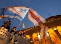 <p>Люди размахивают флагами оппозиции напротив парламента в Тбилиси, 24 марта 2008 года. Около 40 лидеров и активистов оппозиции в Грузии во вторник прекратили продолжавшуюся 17 дней голодовку у здания парламента, однако обещают продолжить акции протеста. REUTERS/David Mdzinarishvili</p>