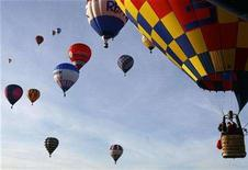 <p>Hot air balloons take part in a mass ascent during the International Balloon Fiesta above the countryside near Bristol in western England, August 10, 2007. REUTERS/Luke MacGregor</p>