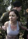 <p>Una manifestante fermata dalla polizia greca all'esterno dello stadio Panathenian ad Atene. REUTERS/ICON/Panagiotis Tzamaros</p>
