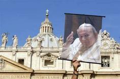 <p>Un fedele con un'immagine di Papa Giovanni Paolo II alla messa per ricordare il terzo anniversario della sua morte, in piazza San Pietro. REUTERS/Alessandro Bianchi</p>