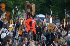 <p>Guitar players raise their instruments after their world record attempt on a field in the southern German town of Leinfelden-Echterdingen June 23, 2007. REUTERS/Alex Grimm</p>