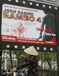 <p>Vietnamita passa pelo cartaz do filme Rambo IV, na capital Hanoi, em 11 de abril de 2008. Photo by Kham</p>