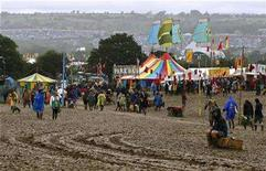 <p>Revellers walk through a muddy field during the Glastonbury music festival in Somerset, south-west England, June 24, 2007. Every morning, the head of Britain's Glastonbury Festival swims 40 laps of a chilly pool. But sales of tickets for this year's show aren't performing quite so swimmingly. REUTERS/Dylan Martinez</p>