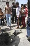 <p>Crianças iraquianas olham pedaço de foguete depois de um ataque aéreo em Basra, 16 de abril. Photo by Atef Hassan</p>